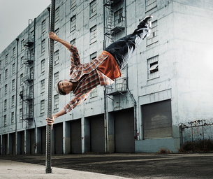 A young man breakdancing, leaping in the air, and stretching out.の写真素材 [FYI02252355]