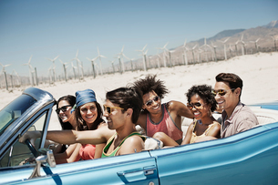 A group of friends in a pale blue convertible on the open road, driving across a dry flat plain surrの写真素材 [FYI02252356]