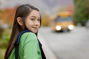 A young girl on the sidewalk, and a yellow school bus with headlights approaching.の写真素材 [FYI02252369]