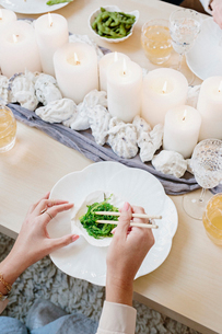 Overhead view of a table with candles and a person using chopsticks to eat green vegetables.の写真素材 [FYI02252374]