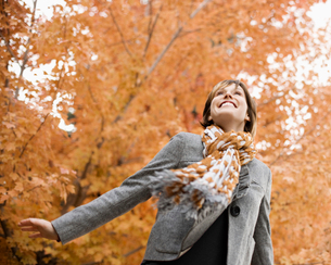 A woman in a jacket and neck scarf against a backdrop of autumn trees in vivid colour.の写真素材 [FYI02252381]