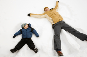 Two people, a man and a child lying in the snow make snow angel shapes.の写真素材 [FYI02252382]