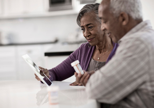 A grey haired couple sitting at a table, looking at information on a digital tablet.の写真素材 [FYI02252386]