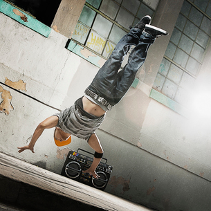 A young man breakdancing on the street of a city, doing a dive moveの写真素材 [FYI02252389]