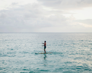 Man stand up paddling in calm waters at duskの写真素材 [FYI02252390]