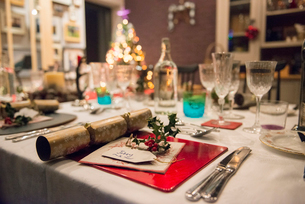 A table laid for a Christmas meal, with silver and crystal glasses and a Christmas tree in the backgの写真素材 [FYI02252392]