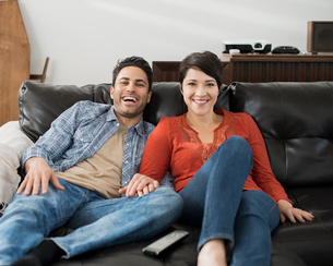 A man and woman sitting on a sofa, side by side, holding hands and watching a screen.の写真素材 [FYI02252410]