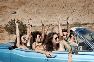 A group of friends in a pale blue convertible on the open road, driving across a dry flat plain surrの写真素材 [FYI02252420]