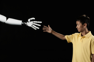A boy reaching up to touch a robotic hand.の写真素材 [FYI02252421]