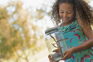A girl holding a glass jar with a butterfly inside it.の写真素材 [FYI02252422]