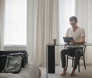 A working day. A man seated at a laptop computer, working in a hotel bedroom.の写真素材 [FYI02252423]
