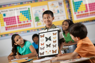 A boy standing in front of classmates, holding up a frame with butterfly specimens.の写真素材 [FYI02252430]