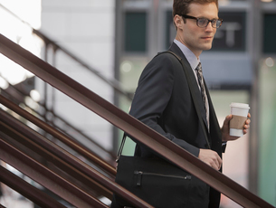 A working day. Businessman in a work suit and tie walking down steps holding a cup of coffee.の写真素材 [FYI02252433]