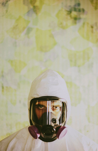 Portrait of a man wearing breathing apparatus and a protective clean suit with a covered head.の写真素材 [FYI02252437]
