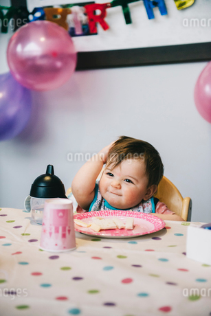 A child, a one year old girl at her birthday party, sitting in a high chair at a table.の写真素材 [FYI02252438]