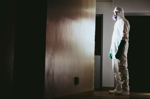 Man wearing a hazardous material protective clean suit, facing bright light in hallwayの写真素材 [FYI02252441]