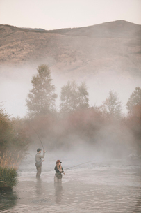A couple, a man and woman standing in mid stream fly fishing in a river.の写真素材 [FYI02252445]