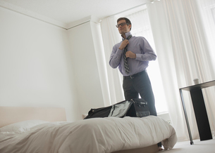 A working day. A man in a shirt tying his tie, in a hotel bedroom.の写真素材 [FYI02252448]