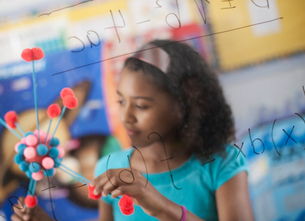 A girl holding a molecular structure and looking at a board of equations and formulae in the classroの写真素材 [FYI02252451]