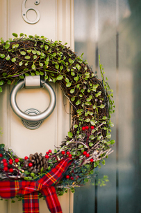 Christmas decorations. A Christmas wreath with a red bow on the front door of a house.の写真素材 [FYI02252452]