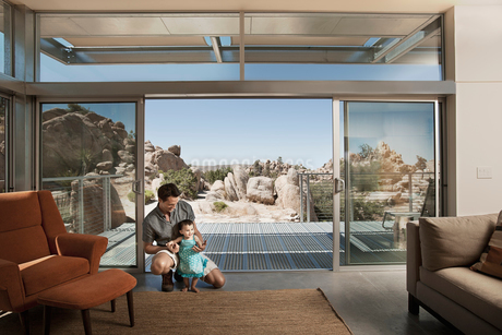 A man and a young child in an ecohouse, a home with large glass walls and view out over the rocky laの写真素材 [FYI02252453]