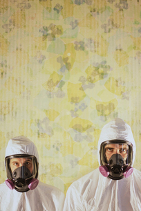 Two men wearing protective hazmat or clean suits in a room, with a background wall decorated with waの写真素材 [FYI02252461]