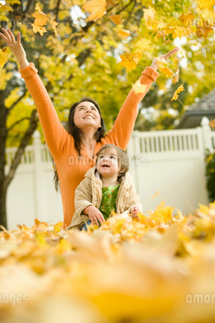 A woman and young child in fallen autumn leaves.の写真素材 [FYI02252468]