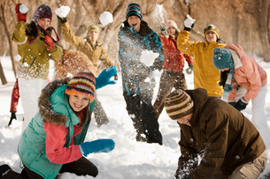 A group of young people, boys and girls having a snowball fight.の写真素材 [FYI02252472]