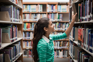 A girl looking at books in a library.の写真素材 [FYI02252476]