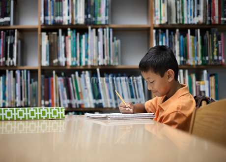 A boy sitting at  table in a school library, using a pencil, studying.の写真素材 [FYI02252477]
