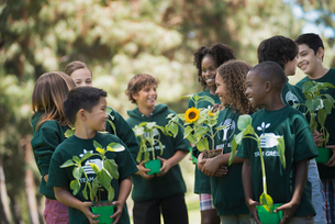 Children in a group learning about plants and flowers, carrying plants and sunflowers.の写真素材 [FYI02252482]