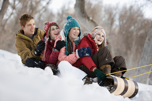 Four young people on a large sledge sliding across the snow, downhill.の写真素材 [FYI02252485]