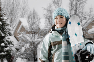 Winter snow. A girl carrying a snowboard.の写真素材 [FYI02252487]