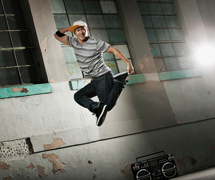 A young man breakdancing on a city sidewalk leaping in the air and striking a pose, looking at the cの写真素材 [FYI02252493]