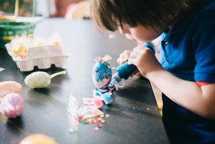 A child decorating eggs at Easter with glitter, glue and paint.の写真素材 [FYI02252494]
