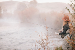 A fisherman, a woman standing on the banks of a river, fly fishing.の写真素材 [FYI02252504]