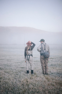Two people walking across a meadow in early morning mist carrying fishing rods.の写真素材 [FYI02252513]