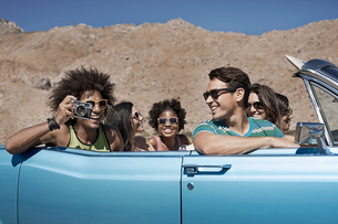 A group of friends in a pale blue convertible on the open road, driving across a dry flat plain surrの写真素材 [FYI02252518]