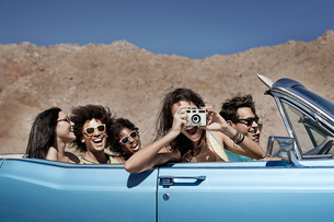 A group of friends in a pale blue convertible on the open road, driving across a dry flat plain surrの写真素材 [FYI02252524]