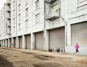 A woman running along an urban road with her arms working and stretching her legs.の写真素材 [FYI02252530]