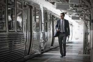 A working day. Businessman in a work suit and tie walking on the platform by a train carriage.の写真素材 [FYI02252532]