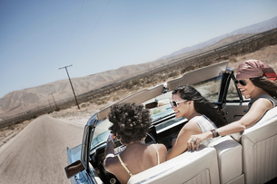 Three young people in a pale blue convertible car, driving on the open road across a flat dry plain,の写真素材 [FYI02252537]