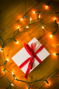 Christmas decorations. Gift box tied with a ribbon and fairy lights.の写真素材 [FYI02252561]