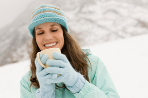 A woman in a blue knitted hat with gloves, holding a cup of coffee.の写真素材 [FYI02252569]