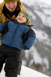 A man with a young child wrapped up against the cold, in the mountains in snow.の写真素材 [FYI02252570]