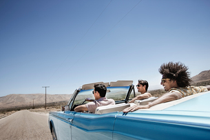 Three young people in a pale blue convertible car, driving on the open road across a flat dry plain,の写真素材 [FYI02252584]