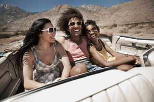 Three young people in a pale blue convertible car, driving on the open road across a flat dry plain,の写真素材 [FYI02252588]