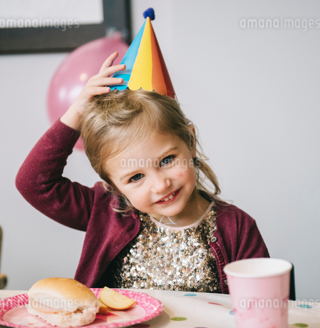 A young girl in a party hat at a birthday party.の写真素材 [FYI02252589]
