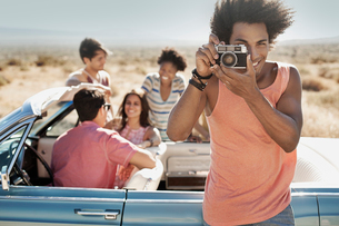 A group of friends by a pale blue convertible on the open road, on a flat plain surrounded by mountaの写真素材 [FYI02252591]