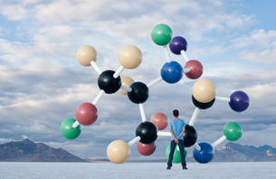 A teenage boy looking upwards at a large molecular structure in the air above him.の写真素材 [FYI02252600]